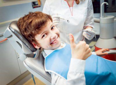 Boy sitting in dental chair smiling