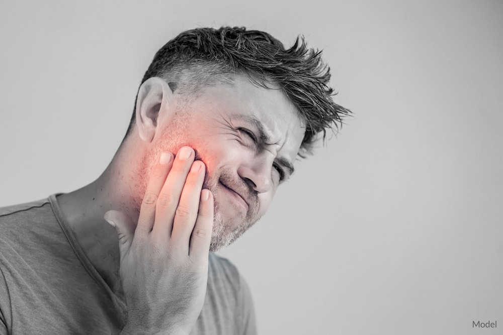 Man experiencing a toothache that requires dental assistance.